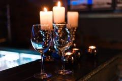 Пустые бокалы и свечи с предпосылкой светов освещения стоковое фото rf