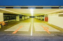 Пустой загоренный подземный интерьер автостоянки под современным торговым центром и стрелки на поле стоковое изображение