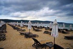 Пустой пустой пляж со сложенными зонтиками пляжа стоковая фотография