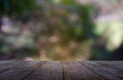 Пустой деревянный стол перед абстрактным запачканным зеленым цветом предпосылки света сада и природы Для дисплея или дизайна прод стоковое изображение