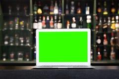Пустой экран ноутбука на бутылке напитка алкоголя нерезкости на счетчике бара в темной предпосылке ночи стоковые изображения
