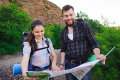 Путешественники друзей ища правильное направление на карте, путешествуя отключение совместно, свобода и активная концепция образа стоковые изображения rf