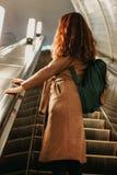 Путешественник девушки молодой женщины курчавый красный главный с рюкзаком и карта в станции метро перед эскалатором стоковые изображения