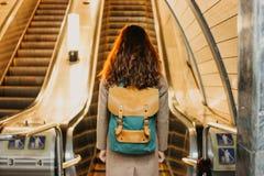 Путешественник девушки молодой женщины курчавый красный главный с рюкзаком и карта в станции метро перед эскалатором стоковое изображение