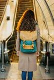 Путешественник девушки молодой женщины курчавый красный главный с рюкзаком и карта в станции метро перед эскалатором стоковые фото