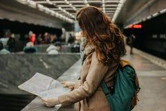 Путешественник девушки молодой женщины курчавый красный главный с рюкзаком и карта в метро стоковые фотографии rf