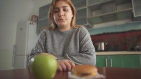 Пухлая девушка думает что она должна съесть вкусный гамбургер или сочное зеленое яблоко выбор трудный Желание для акции видеоматериалы