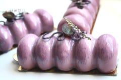 Пурпурные десерты с виноградинами и цветком на золотых каботажных судн стоковое изображение