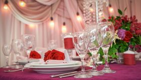 Праздничное украшение таблицы с красными цветками и стеклами стоковая фотография rf