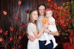 Прекрасная семья усмехаясь и смеясь, представляя на камере, и обнимая один другого для семейного фото стоковые изображения
