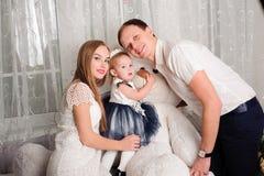 Прекрасная семья усмехаясь и смеясь, представляя на камере, и обнимая один другого для семейного фото стоковые изображения rf
