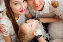 Прекрасная семья усмехаясь и смеясь, представляя на камере, и обнимая один другого для семейного фото стоковое изображение rf