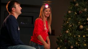 Прелестный маленький ребёнок имея потеху на Рожденственской ночи дома, усмехаясь и бежать вокруг с подарком на рождество видеоматериал