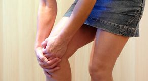 Предпосылка зоны боли красная Маленькая девочка схватила ее колено в пригонке боли Страдать от совместного заболевания стоковые фотографии rf