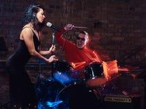 Представление джаз-бэнда Соедините музыкантов - барабанщика и певицы в ночном клубе стоковое фото