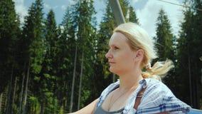 Привлекательная женщина поднимает в подъем лыжи, восхищает красивый пейзаж лета акции видеоматериалы