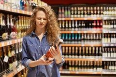 Привлекательная молодая женщина с вьющиеся волосы, носит куртку demin Держит бутылку алкогольного напитка, читает информацию о ви стоковое изображение