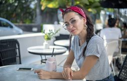 Привлекательная модель в красном bandana и круглых стеклах представляя в кафе улицы, стоковое изображение rf