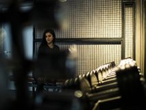 Привлекательная девушка брюнета в черной верхней части и гетры сидит на стенде в сортируя зале на полке с гантелями стоковая фотография