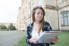 Привлекательная девушка сидит на стенде на университетском кампусе с чашкой кофе и читает тетрадь которая держит в ее руке стоковые фото