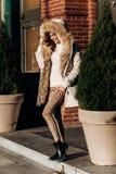 Привлекательная стильная девушка одетая в белом связанном свитере, светлых брюках и светлом пальто с представлениями меха в улицу стоковое фото rf