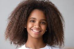 Привлекательная черная девушка подростка усмехаясь смотрящ камеру стоковое фото rf