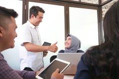 Привлекательный азиатский человек поздравляет его женского сотрудника hijab для ее успеха на офисе стоковое изображение