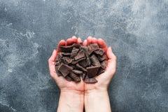Пригорошня задавленного темного шоколада в ладонях рук женщин на темной текстурированной предпосылке стоковые фото