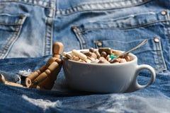 Примите концепцию медицины Доза медицин Деревянный человеческий манекен около таблеток и планшетов чашки полных Коктеиль витамина стоковые фото