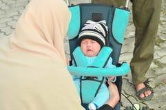 Принимать матери Hijab заботит ее плача младенец в парке с ее супругом стоковые изображения rf