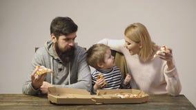 Принципиальная схема питания пицца вкусная Мама, папа и сын едят пиццу совместно на белой предпосылке семья принципиальной схемы  видеоматериал