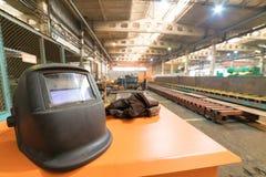 принципиальная схема промышленная Строительная площадка внутри изготовляя плиты Шлем и рабочая одежда на переднем плане стоковые фотографии rf