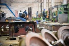 принципиальная схема промышленная Человек используя точильщика на заводе Работники на заводе внутри помещения стоковая фотография rf