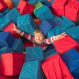 принципиальная схема детства счастливая Мальчик играя с мягкими блоками в развлекательном центре Ребенк в хорошем настроении держ стоковое фото rf