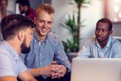 Принципиальная схема сыгранности Молодые творческие сотрудники работая с новым startup проектом в современном офисе Группа людей  стоковое изображение rf
