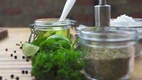 Приправляя черный перец, соль и оливковое масло на деревянном столе Закройте вверх по специям для варить еду на кухонном столе ес акции видеоматериалы