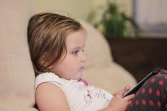 Пристрастившийся ребенок используя телефон стоковое изображение