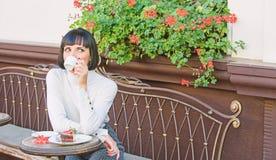 Приятные время и релаксация Брюнет стороны макияжа женщины мечтательный ест предпосылку террасы кафа торта гастрономическо стоковые фотографии rf