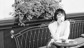 Приятные время и релаксация Брюнет стороны макияжа женщины мечтательный ест предпосылку террасы кафа торта гастрономическо стоковые фото