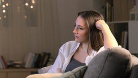 Пробуренная женщина смотря ТВ дома в ночи сток-видео