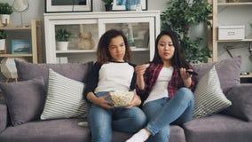 Пробуренные молодые женщины смотрят ТВ совместно дома и едят попкорн сидя на софе в живя комнате Азиатская девушка видеоматериал