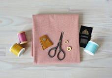 Проверенная ткань, кожаное кольцо, ретро ножницы, деревянные кнопки, выстегивая иглы и красочные потоки стоковые фото