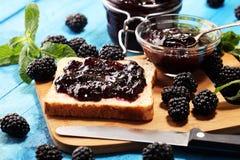 Провозглашайте тост хлеб с домодельным вареньем ежевики или мармелад на таблице служил с маслом на завтрак или завтрак-обедом стоковые фото