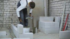 Промежуток времени рабочий-строителя строя внутреннюю стену сток-видео