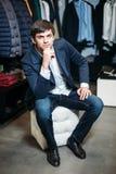 Продажа, покупки, мода, стиль и концепция людей - элегантный молодой человек в пальто сидит и ждет девушек со шлихтой в одежде стоковое фото rf