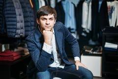 Продажа, покупки, мода, стиль и концепция людей - элегантный молодой человек в пальто сидит и ждет девушек со шлихтой в одежде стоковая фотография