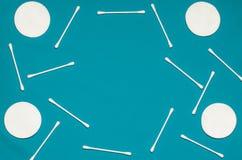Продукты гигиены: пусковые площадки хлопка круга белые и пробирки хлопка на покрашенной предпосылке стоковая фотография