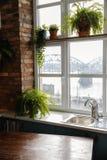 Просторная квартира кухни с конструированной кирпичной стеной и окном смотря на железнодорожный мост в Риге, Латвии стоковые фото