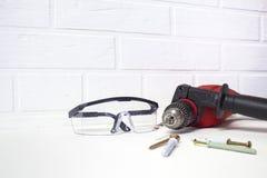 Профессиональный инструмент для сверлить Электрический сверлильный аппарат с защитными стеклами на предпосылке кирпичной стены стоковое фото