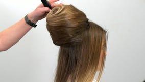 Профессиональный парикмахер демонстрирует законченный стиль причесок и завершает поправки видеоматериал